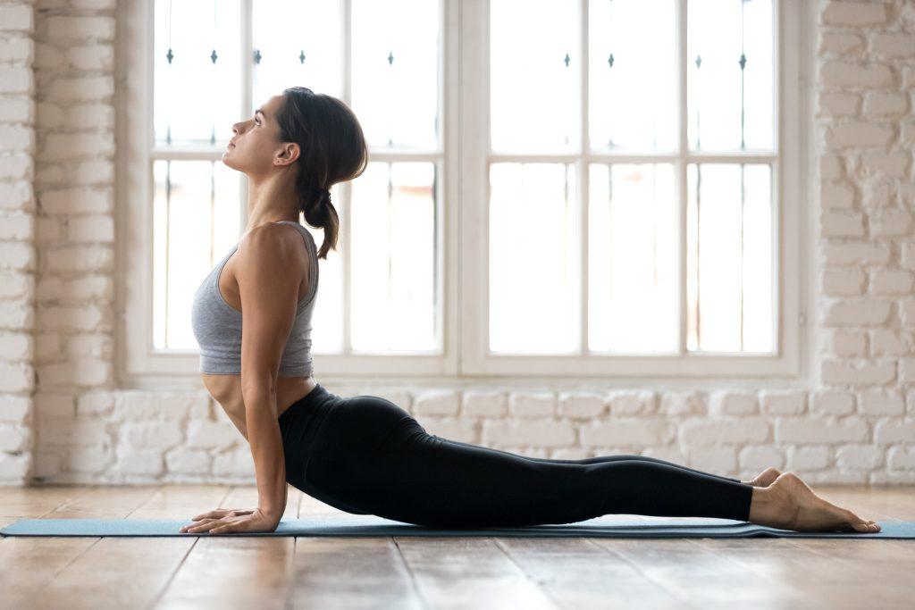 Local Yoga Studios - Young sporty woman practicing yoga, doing upward facing dog exercise, Urdhva mukha shvanasana pose, working out, wearing sportswear, pants and top, indoor full length, white yoga studio