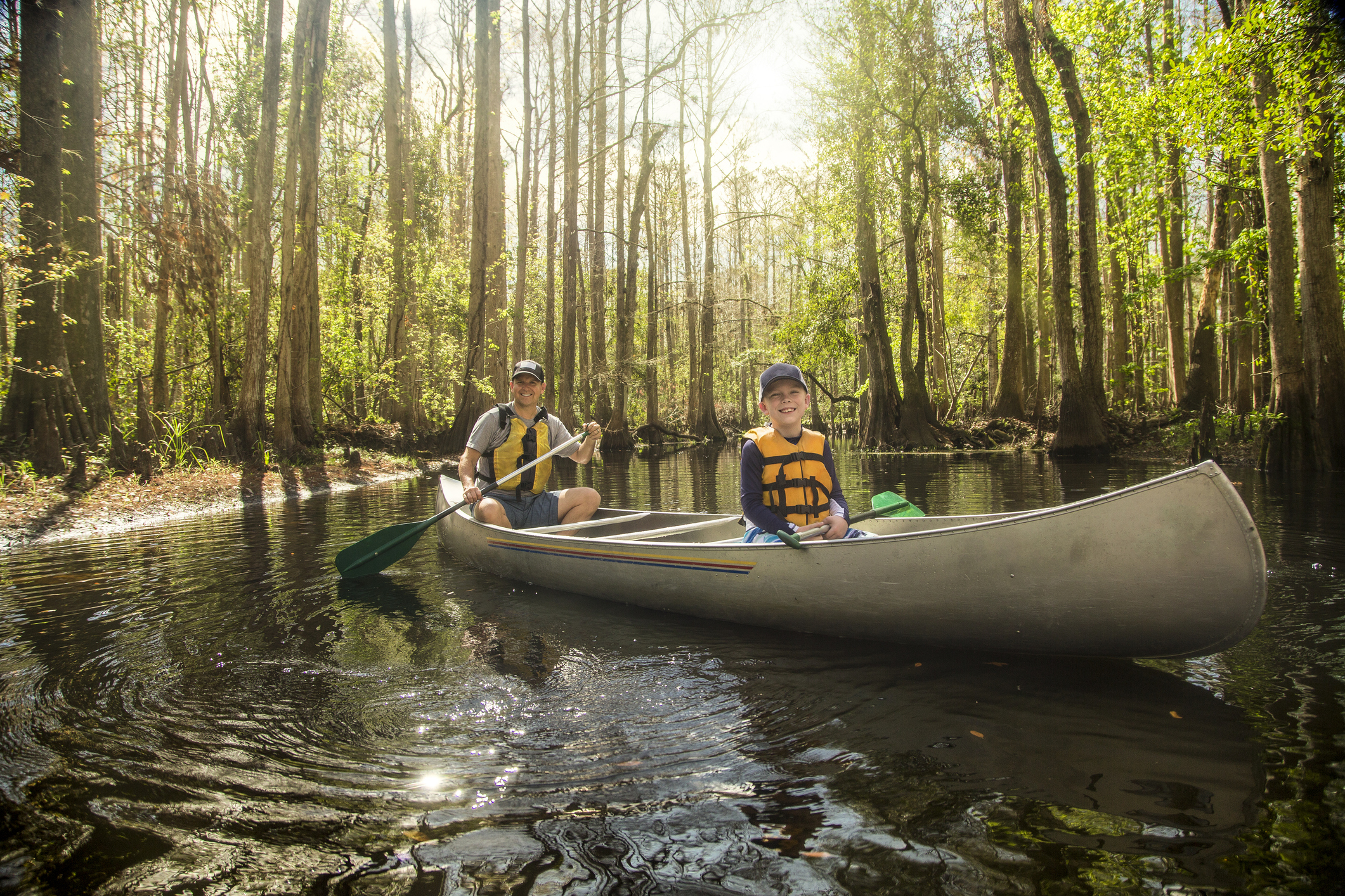 Handsome father and his son kayaking together in a cypress swamp river in beautiful Florida. Smiling and having fun together in nature representing condos for sale in bradenton fl