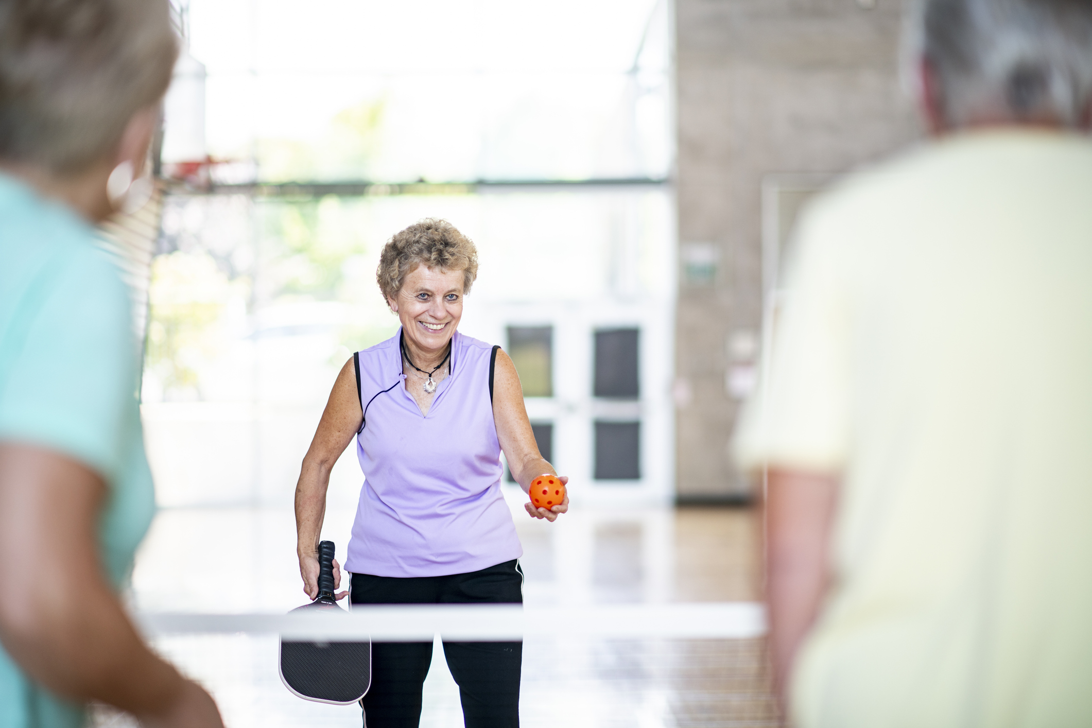 A group of seniors are playing pickleball in a fitness center. One woman is about to serve.