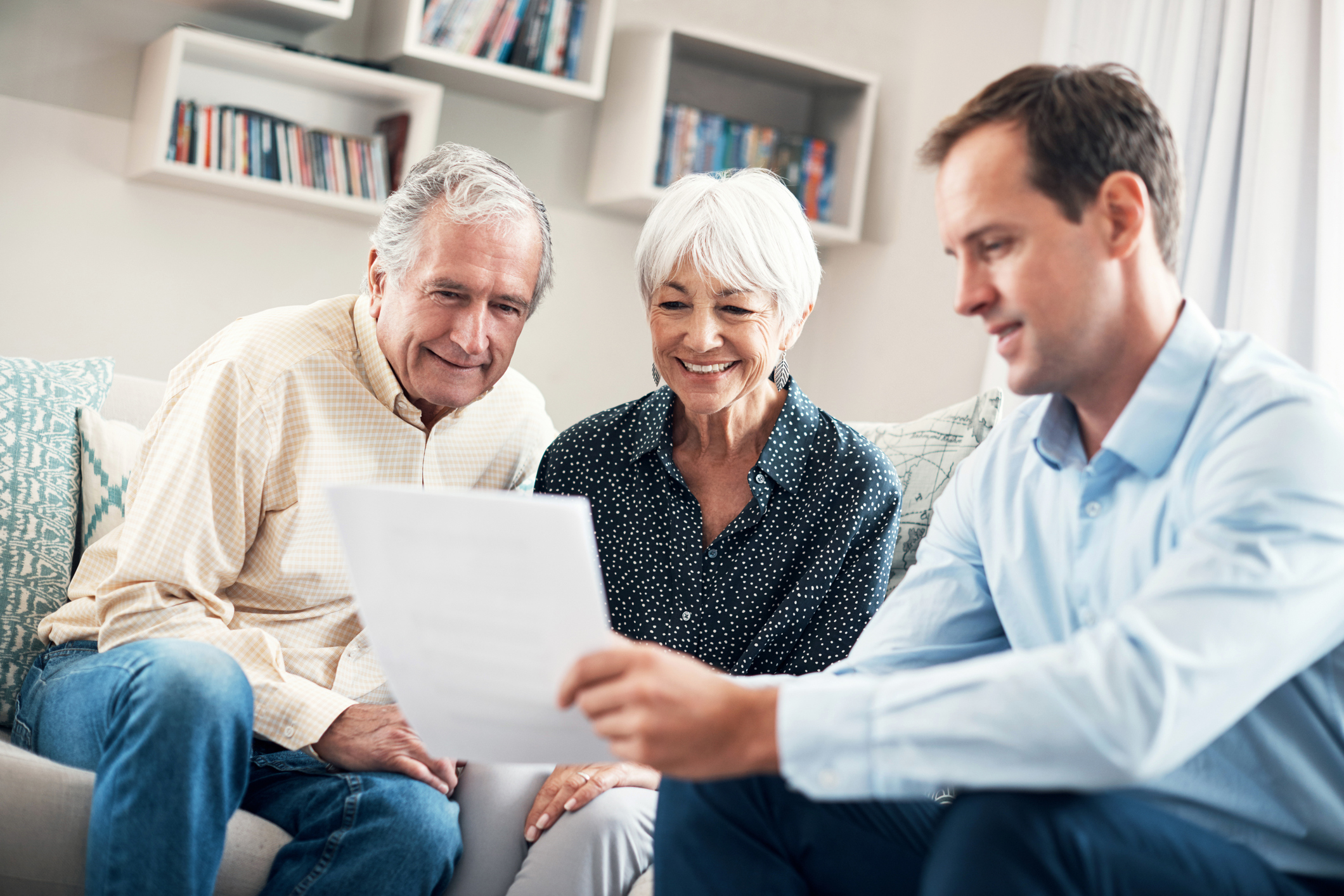 an older couple smiling looking at realtor's paper while they are thinking about buying condos for sale in Bradenton, Florida