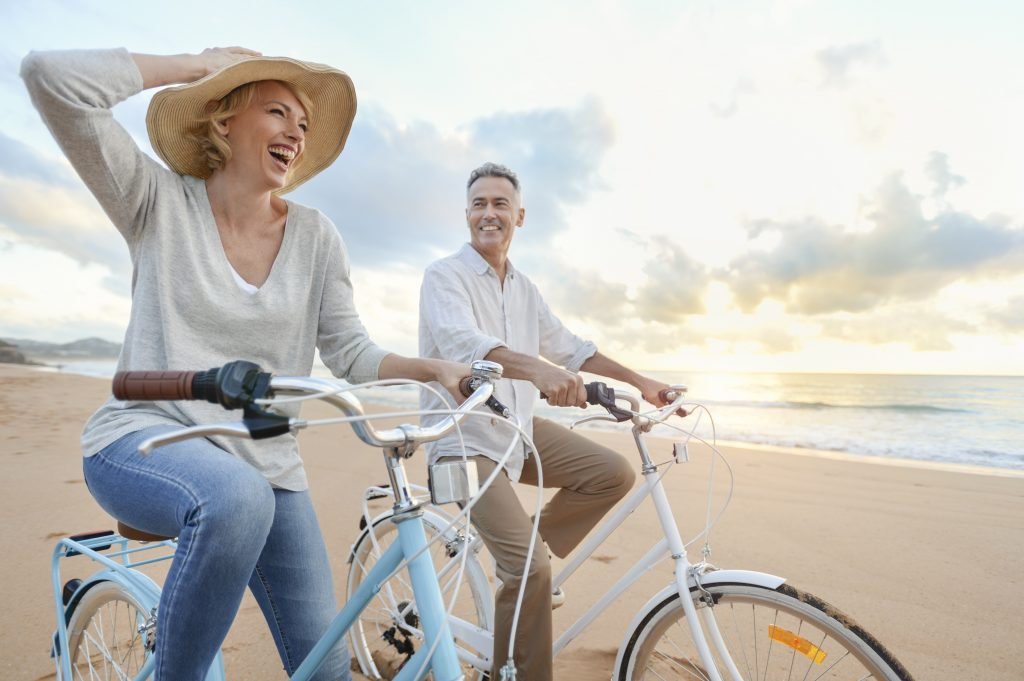 condo living is perfect for baby boomers - two older people riding bikes on the beach