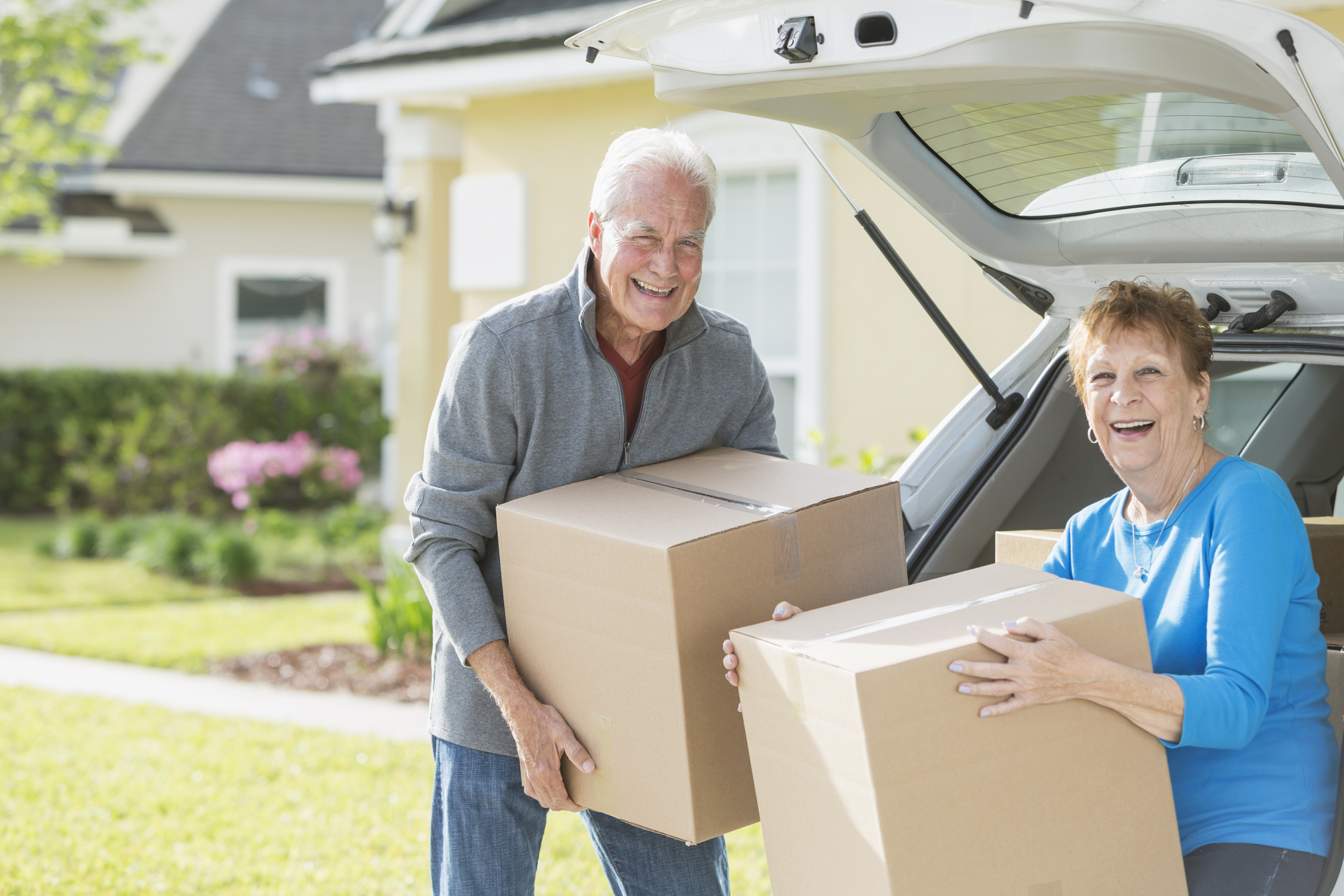 A happy senior couple moving boxes into or out of the back of their car. They are moving house, perhaps downsizing. They are looking at the camera, smiling representing downsizing and condos in bradenton.