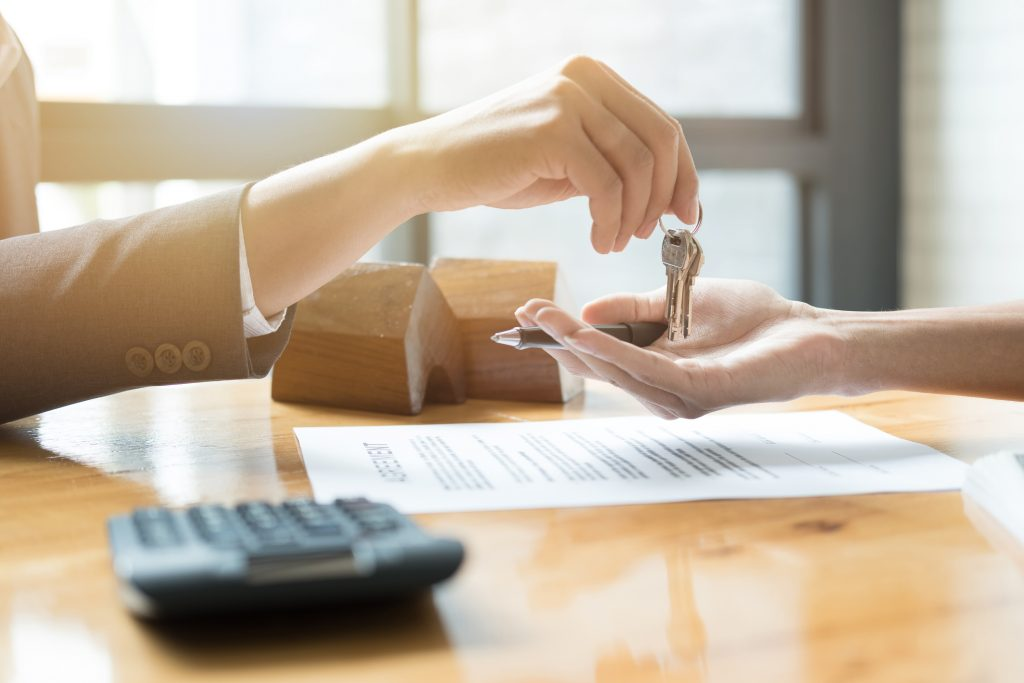 condominium buying guide - estate agent giving house keys to man and sign agreement in office