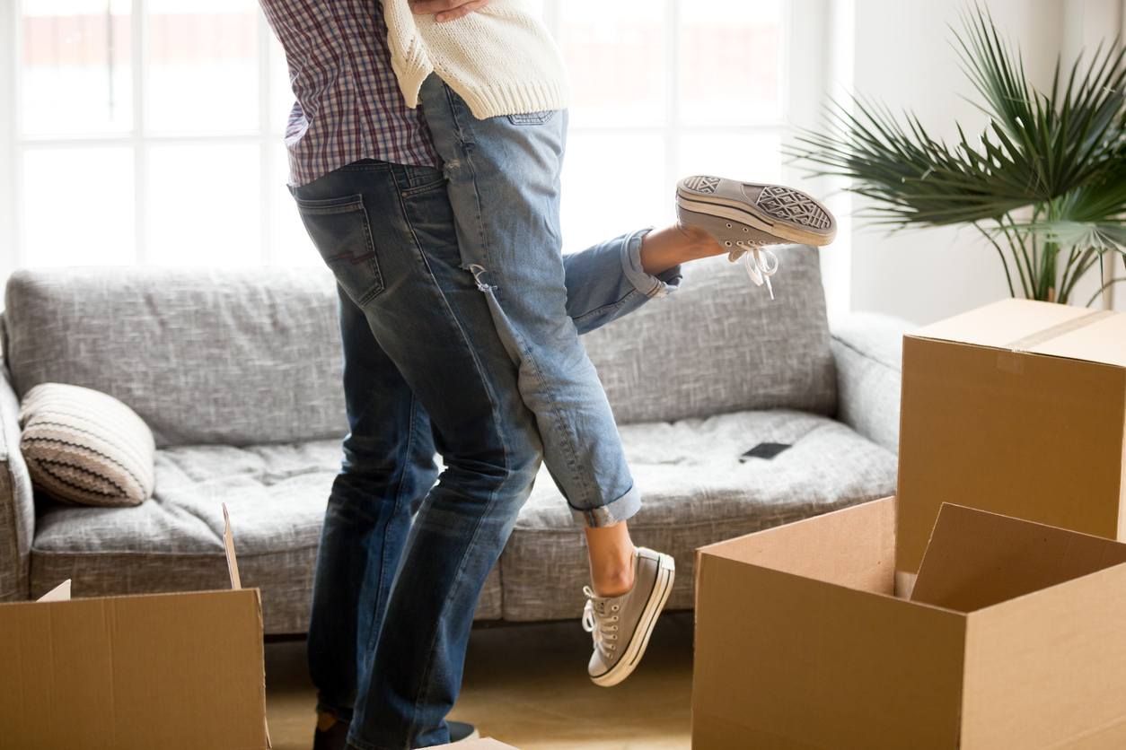 condo living - Man lifting woman standing among cardboard boxes, close up view