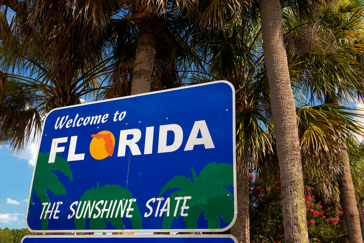 moving to Florida Welcome to Florida sign with palm trees in background
