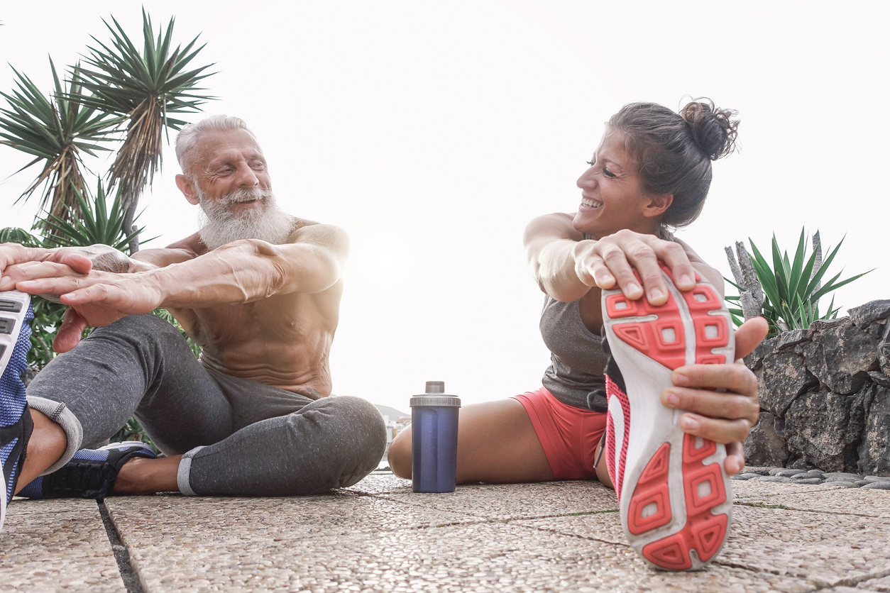 active and fit - Happy fitness friends doing legs stretching exercises together in outdoor area - Sporty couple workout while laughing looking each other during a sunny day - Fitness and sport lifestyle concept