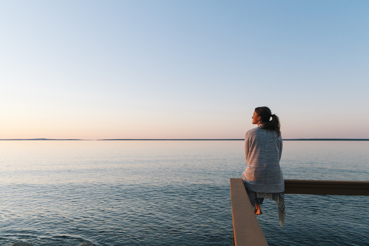 Young woman sitting on edge looks out at view - waterfront living a concept