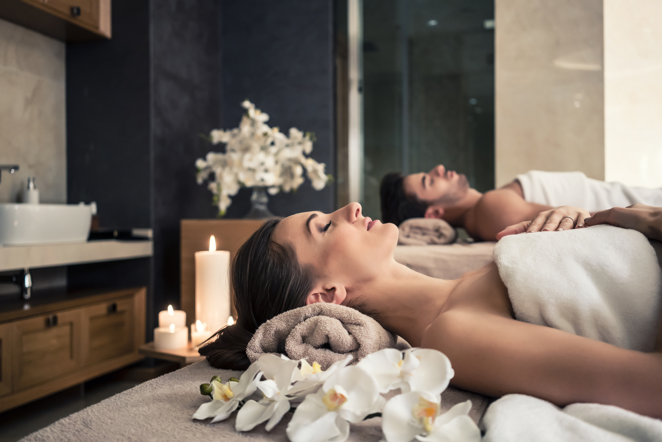 Young man and woman lying down on massage beds at Asian luxury spa and wellness center representing relaxing in luxury